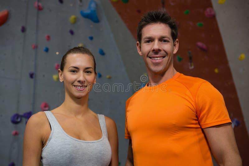 Портрет уверенно спортсменов против взбираясь стены в спортзале стоковые фотографии rf