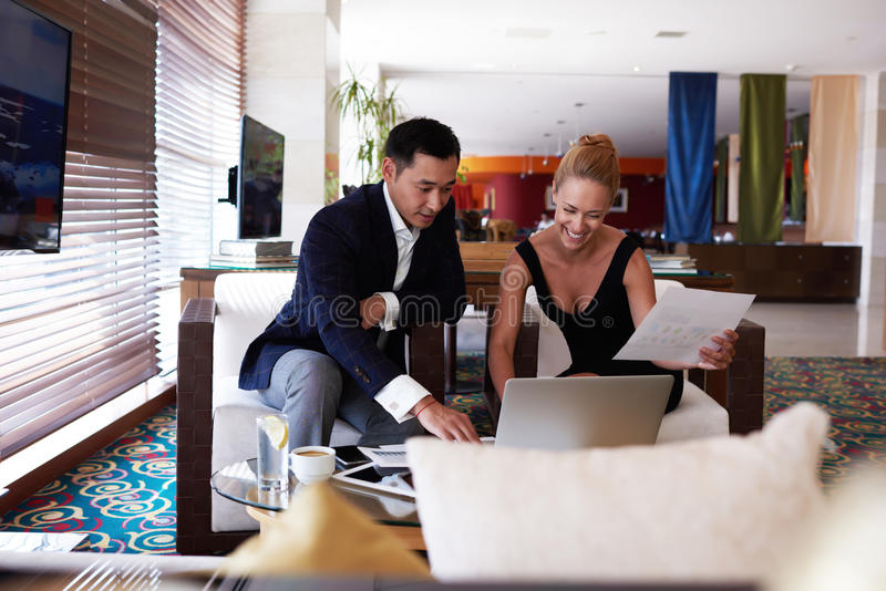 Портрет уверенно человека и женщины наблюдая совместно рабочие планы пока сидящ с портативным компьютером в интерьере офиса стоковое изображение rf