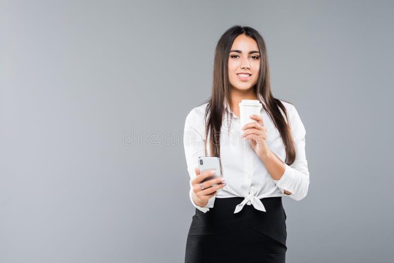 Портрет удовлетворенной молодой бизнес-леди используя мобильный телефон пока держащ, что чашка кофе пошла изолированный над белой стоковые изображения rf