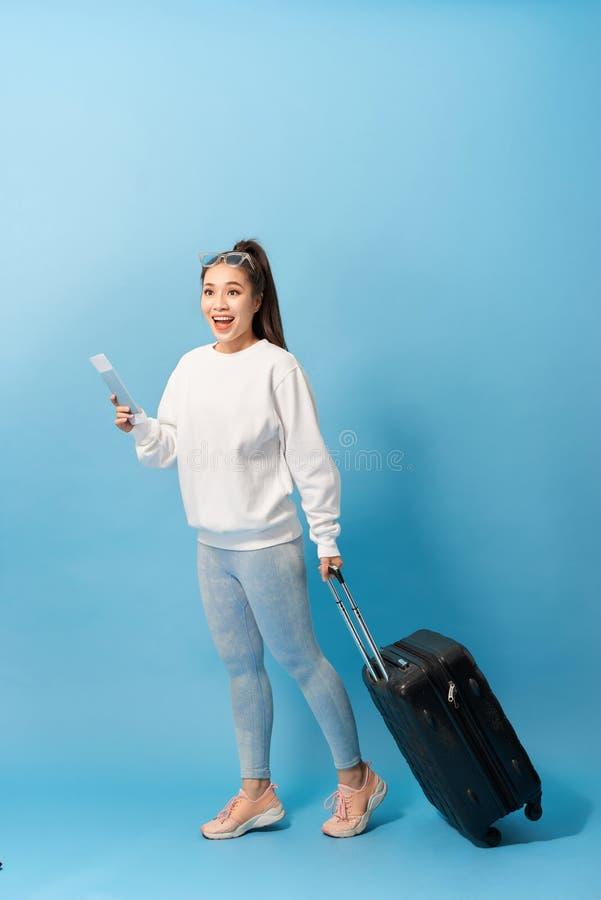 Портрет ультрамодного положения маленькой девочки с чемоданом и паспортом удержания с билетами, над голубой предпосылкой стоковое изображение rf