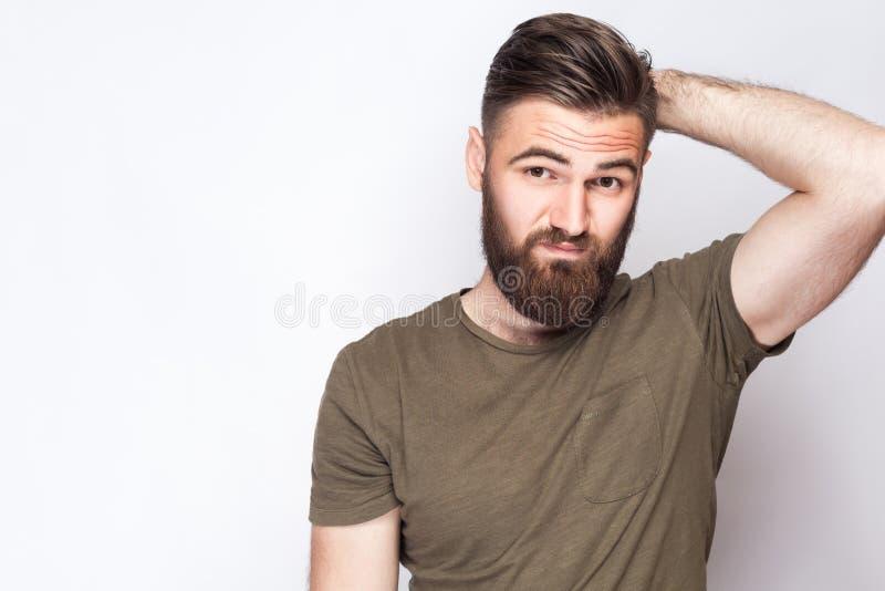 Портрет думать бородатый человек с темной ой-зелен футболкой против света - серой предпосылки стоковые фото