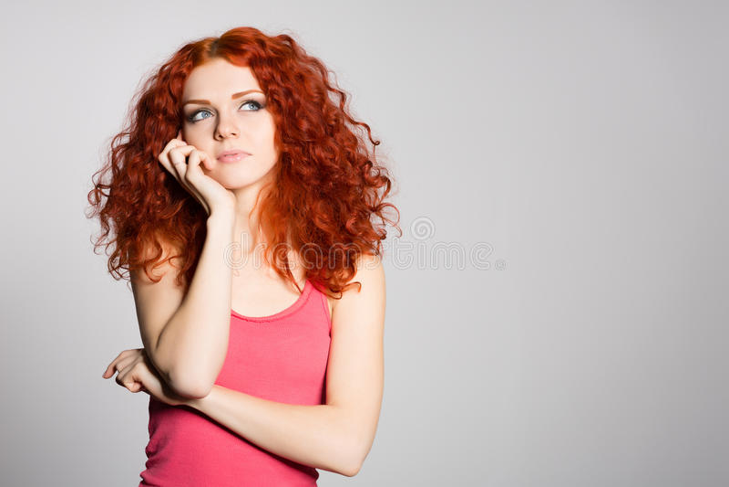 Портрет думая красная с волосами молодая женщина стоковые фото