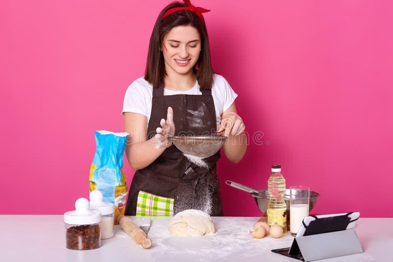 Портрет умелого талантливого повара кладя муку через сетку на половинный готовый пирог с изюминкой Представления брюнета милые мо стоковое фото
