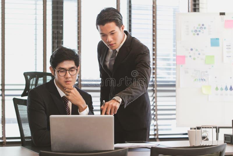 Портрет умных бизнесменов обсуждая проект в компьтер-книжке на мне стоковые изображения