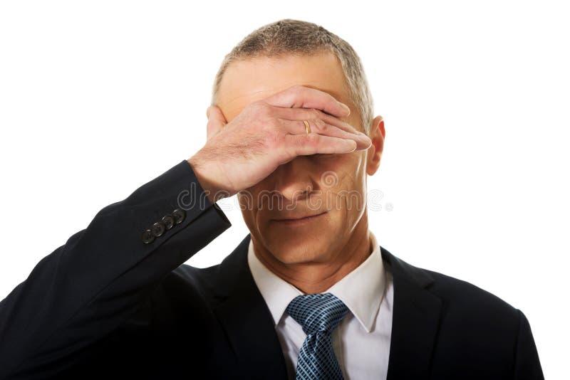 Портрет усиленного бизнесмена покрывая его сторону стоковое фото rf
