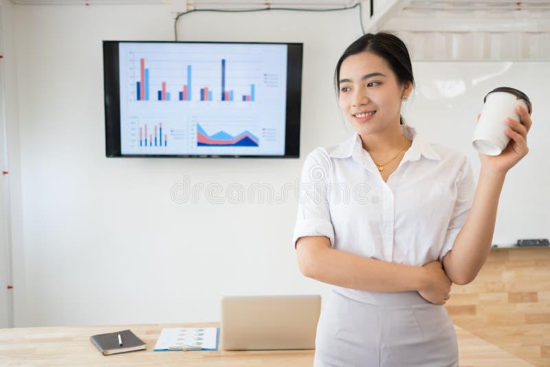 Портрет усмехаться довольно молодая бизнес-леди на рабочем месте, стоковое изображение