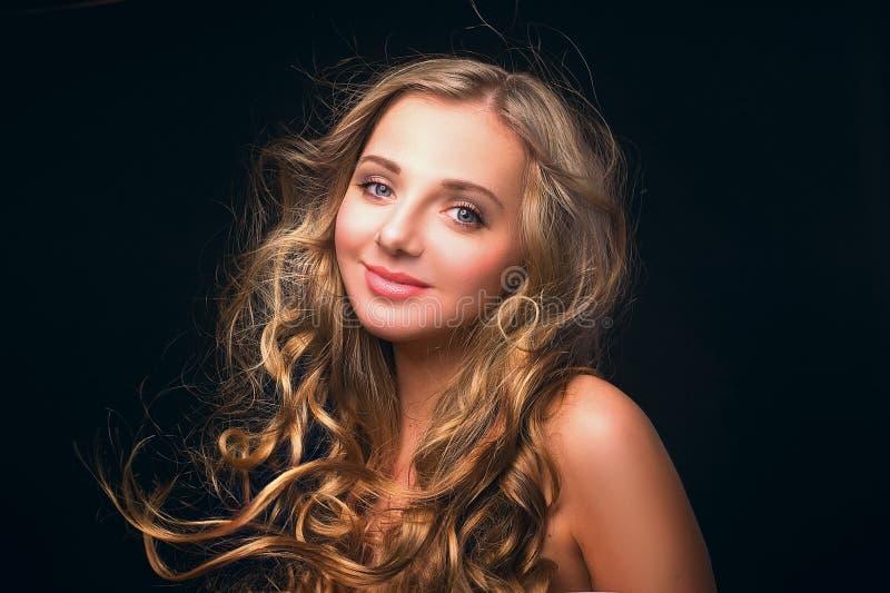 Портрет усмехаться, длинная с волосами, молодая, красивая, белокурая женщина при ее волосы порхая на ветре стоковые изображения rf