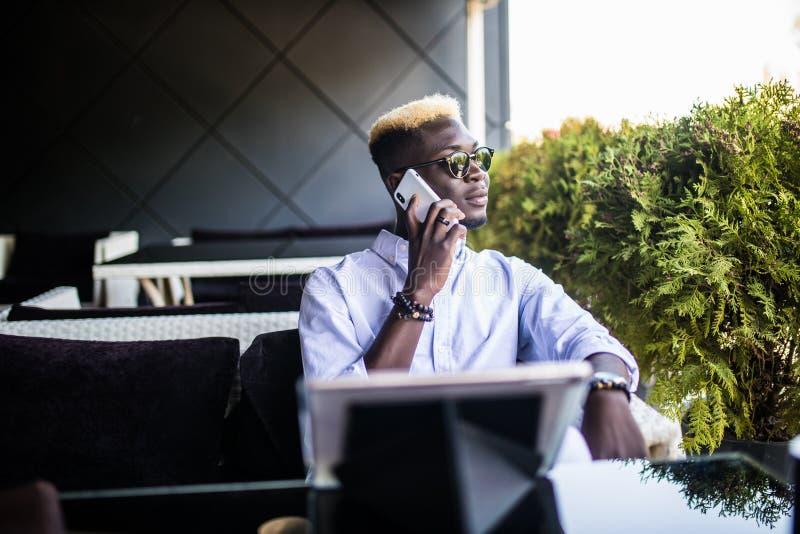 Портрет усмехаясь афро американского человека говоря на сотовом телефоне пока сидящ на кафе с планшетом стоковые фотографии rf