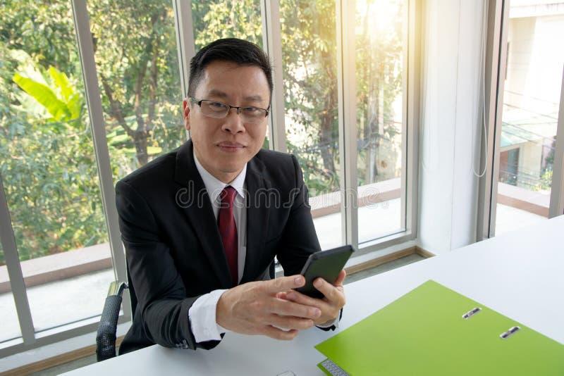 Портрет усмехаясь бизнесмена в мобильном телефоне костюма сидя осматривая проверяя зеленый документ стоковые фото