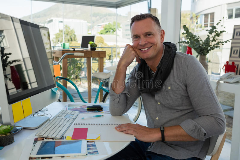 Портрет усмехаясь бизнесмена сидя на столе стоковое изображение