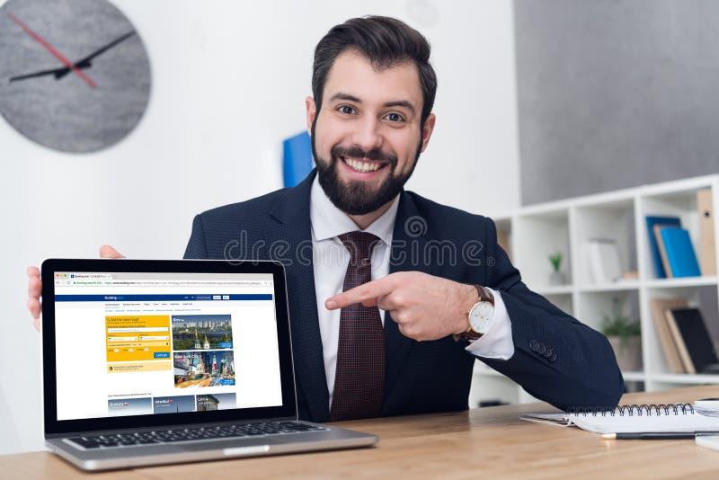 портрет усмехаясь бизнесмена указывая на компьтер-книжку на рабочее место стоковая фотография rf
