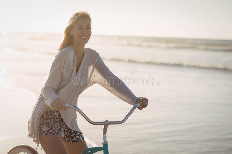 Портрет усмехаясь велосипеда катания женщины на пляже стоковое изображение rf