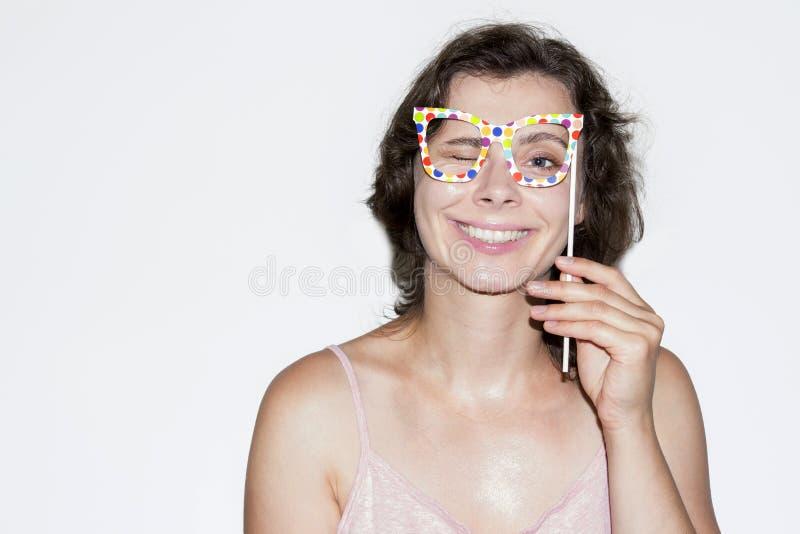 Портрет усмехаясь девушки брюнет с маской стекел на ручке Счастливая молодая кавказская женщина держа жизнерадостную маску с стек стоковые фотографии rf