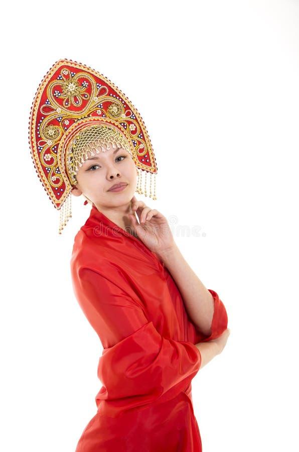 Портрет усмехаясь девушки в kokoshnik & x28; headdress& x29; и красное платье на белой предпосылке стоковые изображения