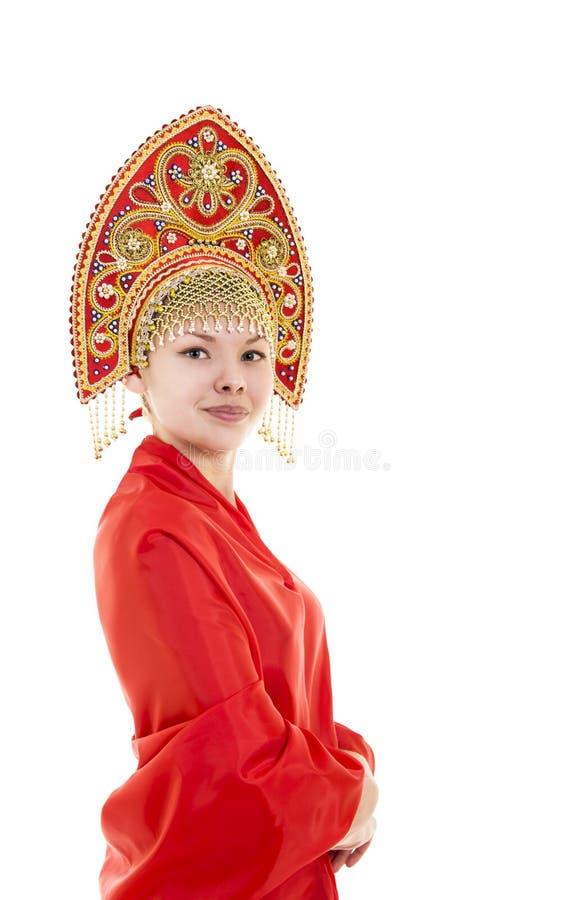 Портрет усмехаясь девушки в kokoshnik & x28; headdress& x29; и красное платье на белой предпосылке стоковое фото