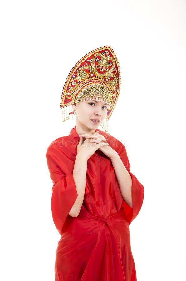 Портрет усмехаясь девушки в kokoshnik & x28; headdress& x29; и красное платье на белой предпосылке стоковые фотографии rf