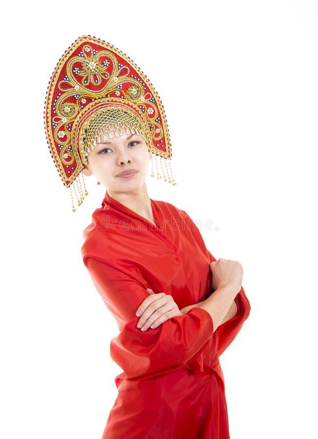 Портрет усмехаясь девушки в kokoshnik & x28; headdress& x29; и красное платье на белой предпосылке стоковые фото