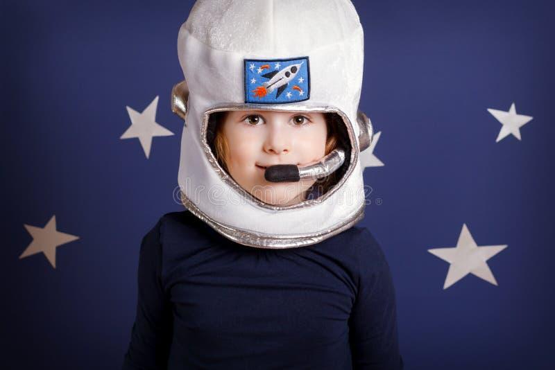 Портрет усмехаясь девушки одетый как астронавт на сини стоковые фотографии rf