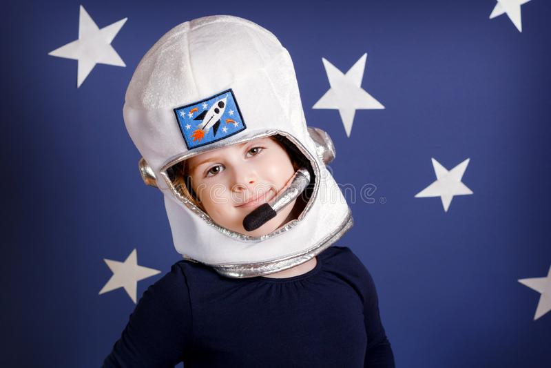 Портрет усмехаясь девушки одетый как астронавт на сини стоковые фото