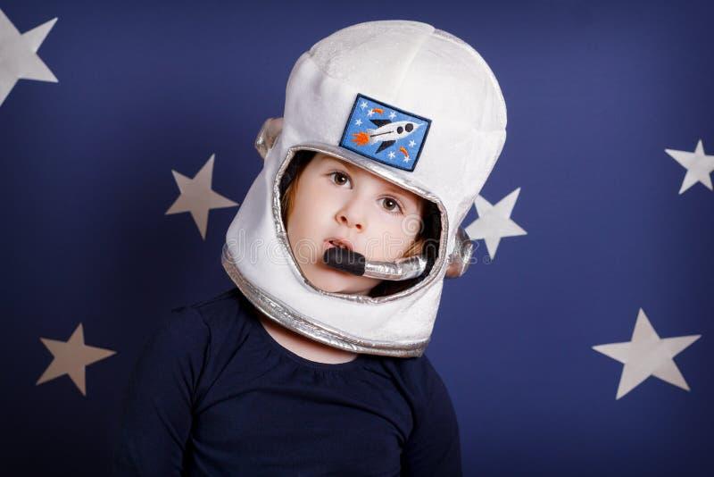 Портрет усмехаясь девушки одетый как астронавт на сини стоковые изображения