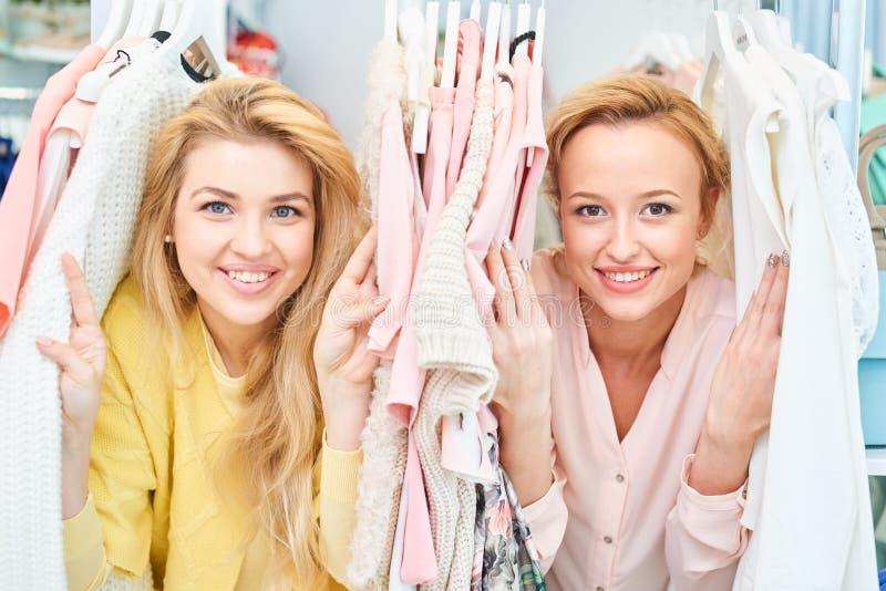Портрет усмехаясь девушек в магазине с одеждами стоковые фотографии rf