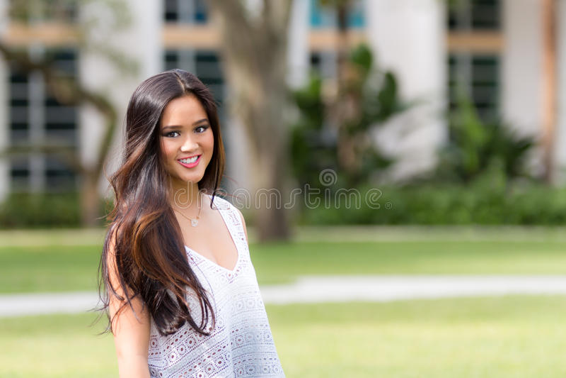 Портрет усмехаясь девушки детенышей довольно азиатской с длинным коричневым цветом ha стоковая фотография rf