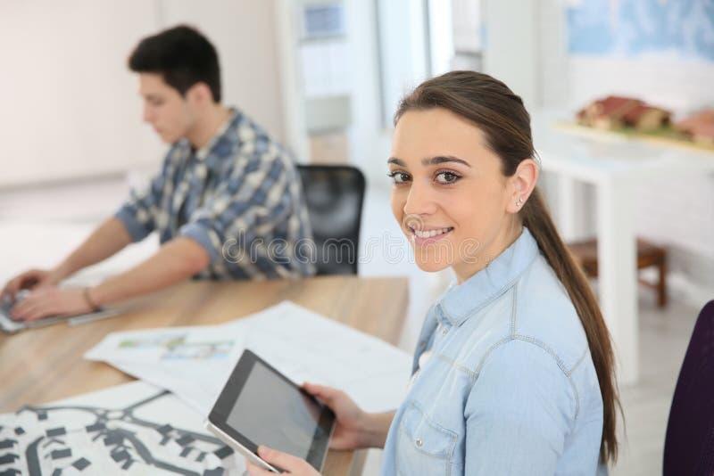 Портрет усмехаясь девушки студента используя цифровую таблетку в классе стоковые фотографии rf