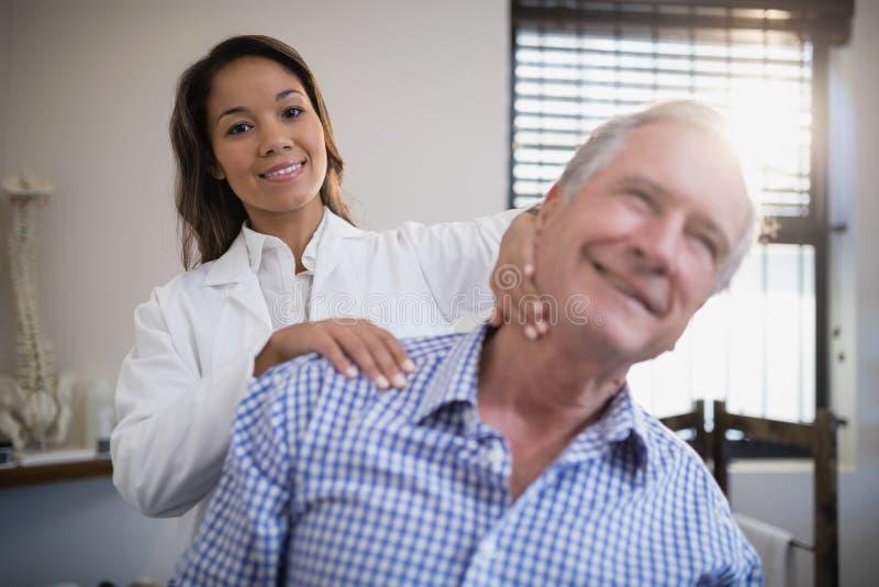 Портрет усмехаясь женского терапевта давая массаж шеи к старшему пациенту стоковые фото