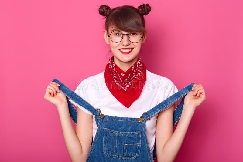 Портрет усмехаясь женщины со смешными пуками, носит футболку, прозодежды джинсовой ткани и bandana на шеи, имеет зубастую улыбку, стоковое изображение