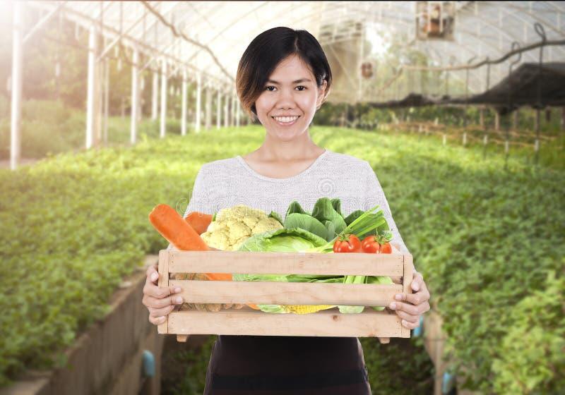 Портрет усмехаясь женщины штата держа деревянную коробку с свежей стоковое изображение