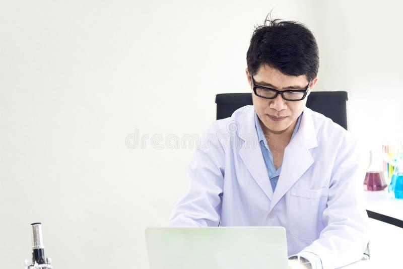 Портрет усмехаясь зрелого ученого в белом пальто с glas стоковые фото