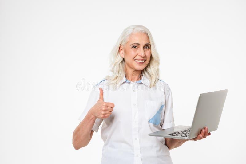 Портрет усмехаясь зрелой женщины держа портативный компьютер стоковые фото