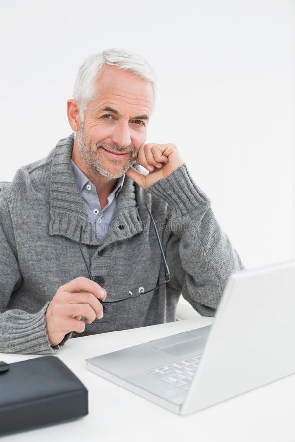 Портрет усмехаясь зрелого человека с компьтер-книжкой на столе стоковое изображение rf