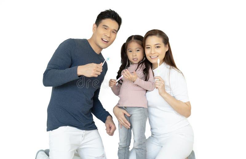 Портрет усмехаясь зубов и усмехаться счастливой азиатской семьи чистя щеткой на камере изолированной на белизне Здоровые зубы стоковая фотография rf