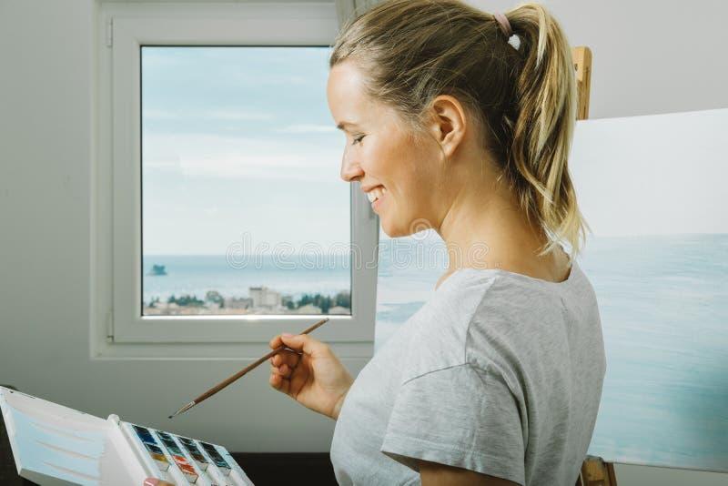 Портрет усмехаясь картины чертежа молодой женщины в домашней студии, стоковые изображения rf