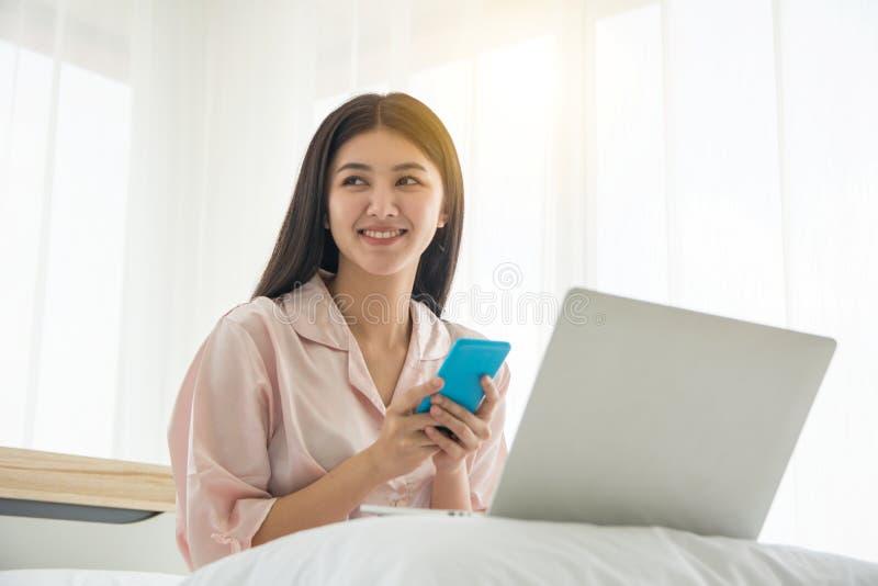 Портрет усмехаясь красивого бодрствования дамы вверх по осматривая мобильному телефону и работы с тетрадью на кровати с космосом  стоковая фотография