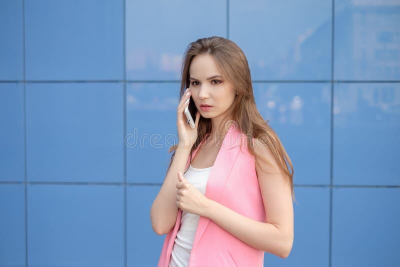 Портрет усмехаясь красивой женщины говоря на телефоне стоковые фото