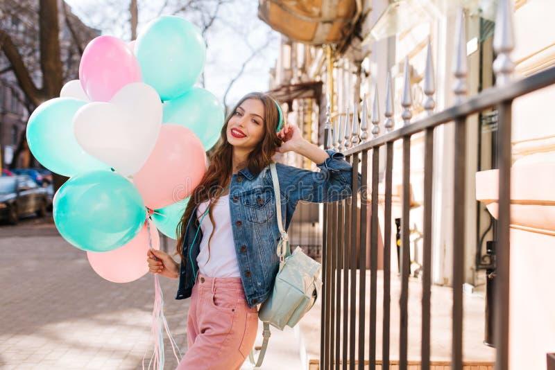 Портрет усмехаясь куртки джинсовой ткани молодой женщины нося и стильных брюк представляя с воздушными шарами дня рождения Привле стоковые изображения rf