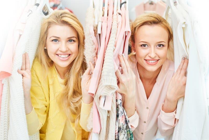 Портрет усмехаясь магазина девушек с одеждами стоковое фото rf