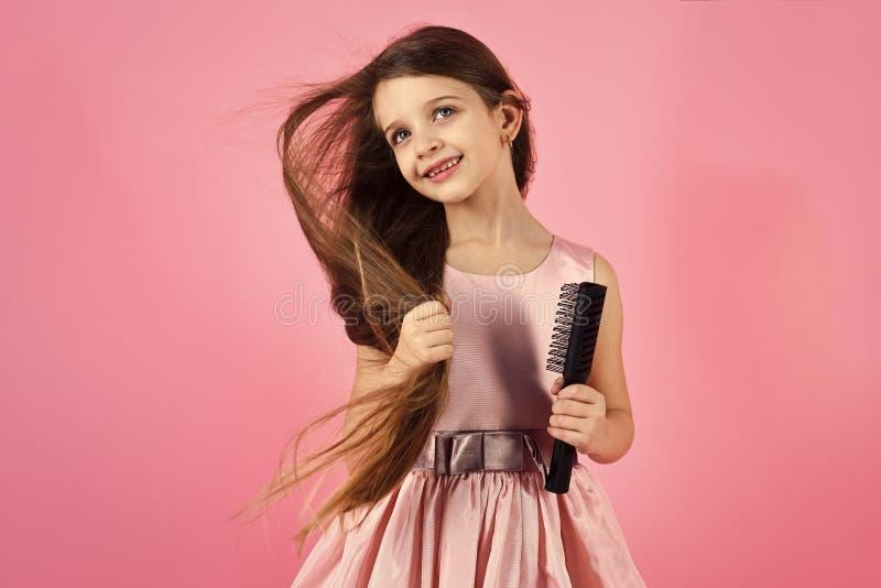 Портрет усмехаясь маленькой девочки чистя ее волосы щеткой стоковые фотографии rf