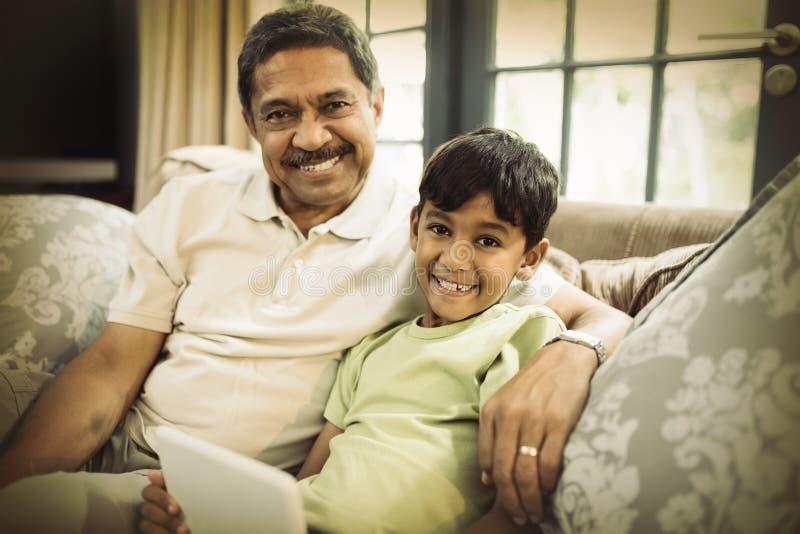 Портрет усмехаясь мальчика при дед держа цифровую таблетку пока сидящ дома стоковые фотографии rf