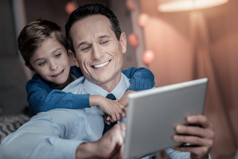 Портрет усмехаясь мальчика тот обнимать его папы стоковое фото rf