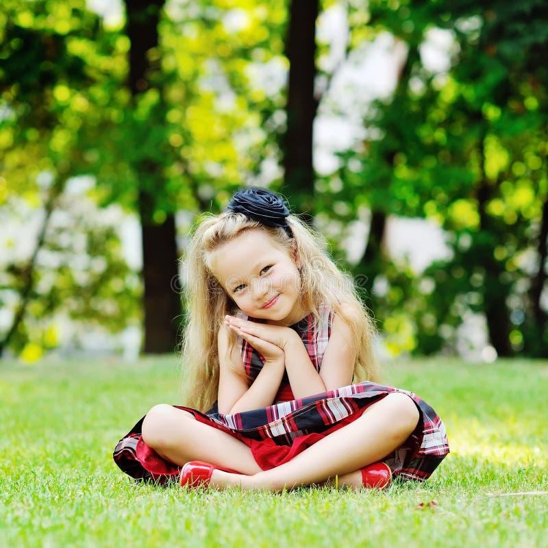 Портрет усмехаясь маленькой девочки сидя на зеленой траве стоковые изображения