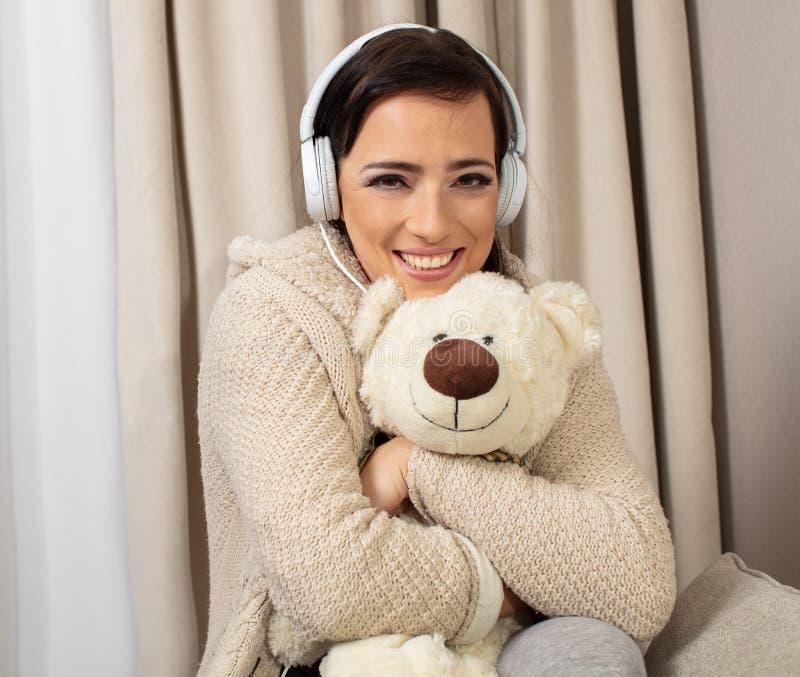 Портрет усмехаясь милой женщины представляя с наушниками и teaddy медведем стоковое изображение