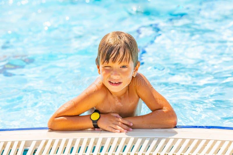 Портрет усмехаясь милых заплывания мальчика и потехи в бассейне, крупного плана иметь стоковые изображения