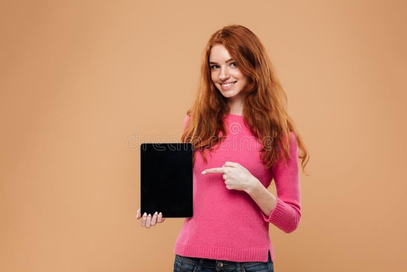 Портрет усмехаясь молодой девушки redhead указывая палец стоковые изображения