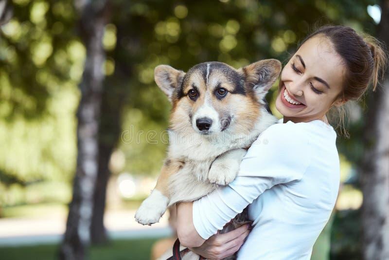 Портрет усмехаясь молодой женщины держа милый Corgi валийца собаки в парке outdoors стоковое изображение