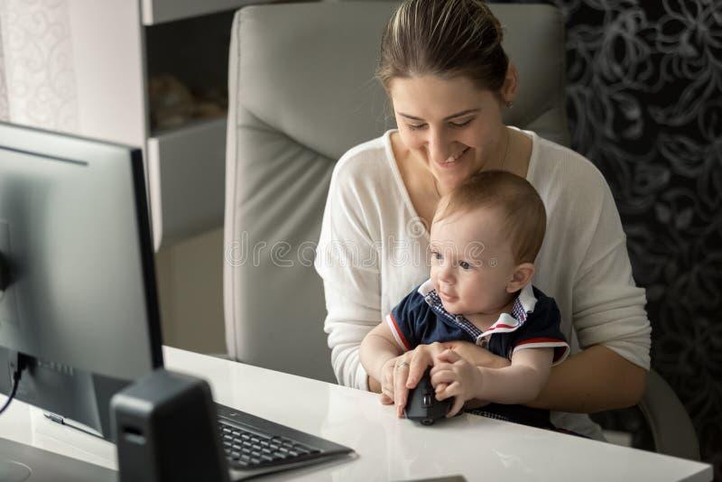 Портрет усмехаясь молодой матери показывая ее сыну младенца как использовать мышь компьютера стоковые фото