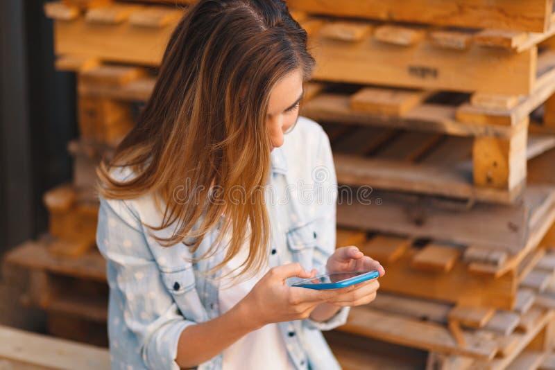 Портрет усмехаясь молодой случайной милой женщины смотря mobil стоковые изображения rf