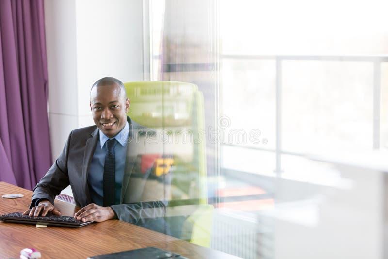 Портрет усмехаясь молодого бизнесмена используя клавиатуру компьютера на столе в офисе стоковые изображения rf